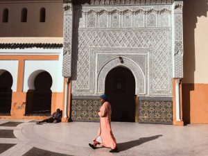 Islamic person in traditional clothes in front of a mosque.