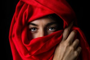 A woman hiding her face with a red scarf is a usual sight after moving to Bahrain with your family.