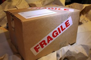 A cardboard box with fragile written on it as not taking good care of fragile items is one of the most common packing mistakes to avoid.