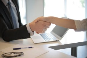 Two people shaking hands and making a deal about international relocation.