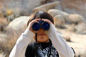 Kid looking through binoculars.