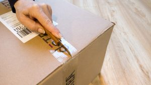 A woman opening a cardboard box, one of the sustainable packing materials.