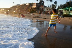 A boy playing at the beach in Newport Beach