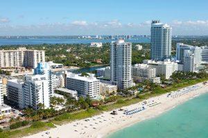 Miami coastline with white sand, blue sea and tall, white buildings