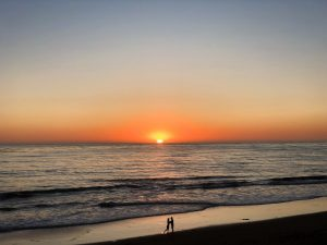 A couple enjoying the sunset on the beach. One of the 7 things Californians miss most when they move is certainly the Pacific Ocean.