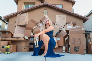 a woman in blue dress in front of moving boxes